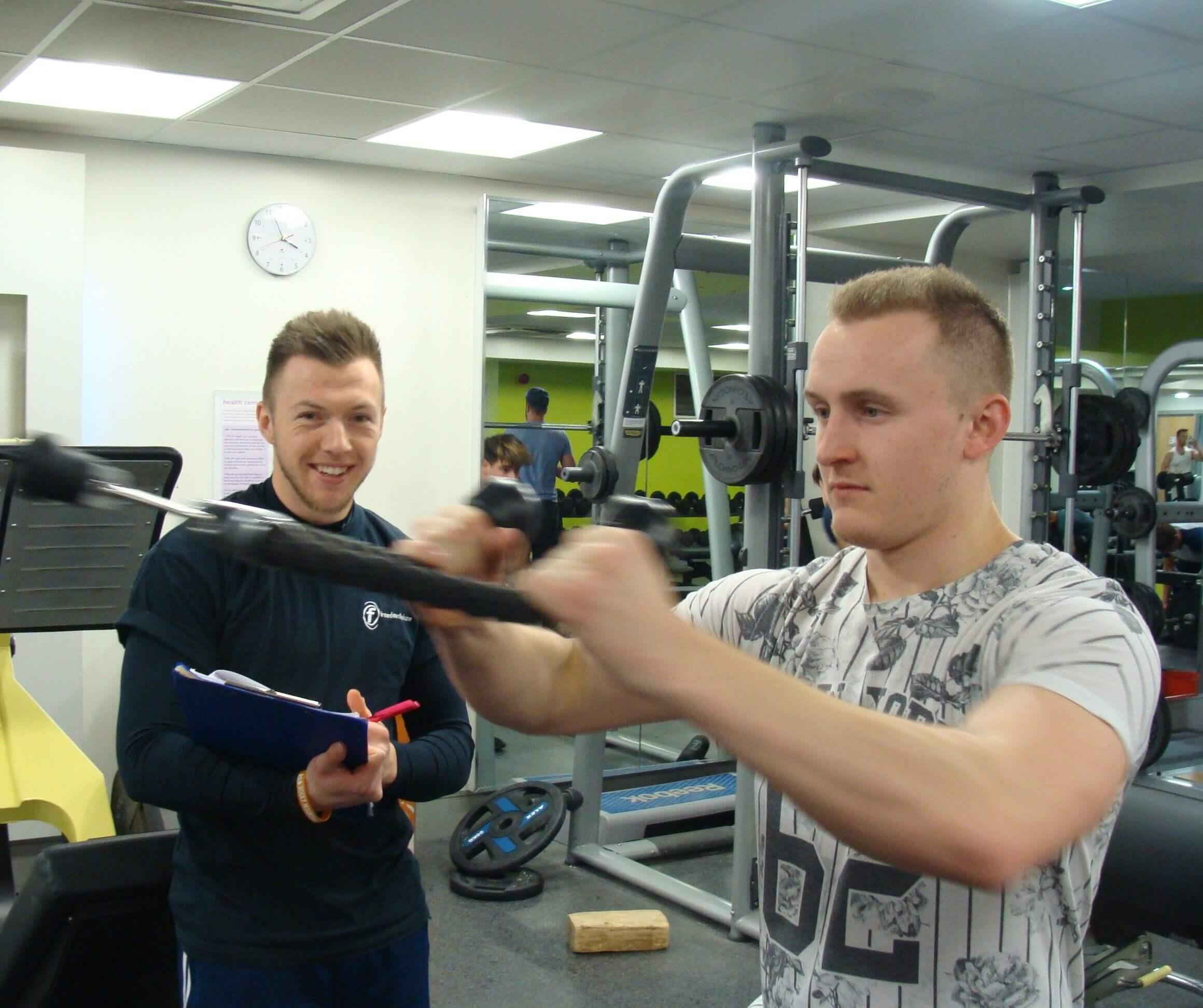 在健身房和私人教练一起锻炼